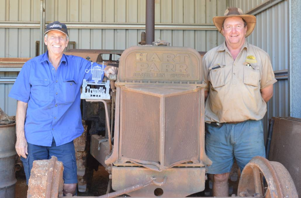 GOOD OLD DAYS: Digger Anderson (left) and Donald Wright (right) with an antique Hart Parr tractor and a prototype of the Tractor Pull trophy.